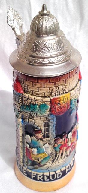 """Der Bierkrug ist liebevoll im Detail gestaltet und mit einem Zinndeckel versehen. Beschriftung: """"Schöne Weiber sind gute Zeitvertreiber"""""""